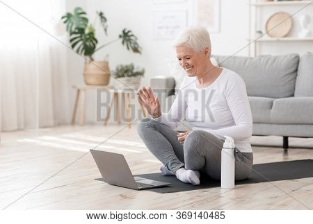 Smiling Senior Woman Training At Home Online Via Laptop, Waving Hand At Camera, Greeting Fitness Ins
