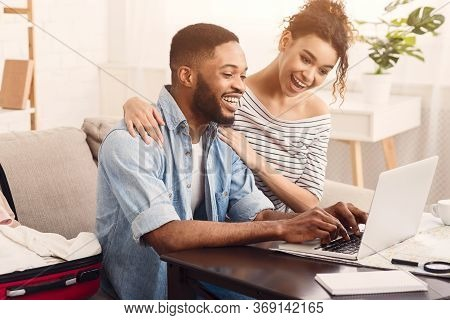 Planning Honeymoon. Joyful African American Couple Using Laptop Sitting At Table Indoors.
