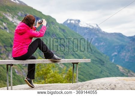 Tourism Adventure And Travel. Female Tourist Hiker Sitting On Bench In Stone Mountains Taking Photo
