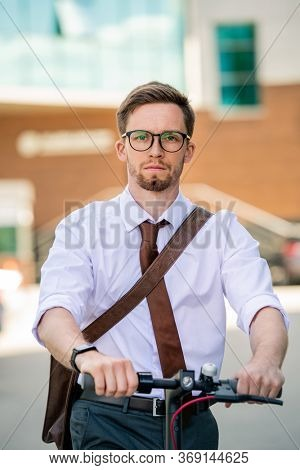 Young serious businessman in eyeglasses and formalwear going home by bicycle while moving forwards in front of camera outdoors