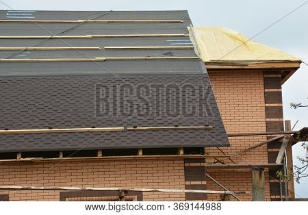 A Close-up On A Roofing Construction With Asphalt Roof Shingles Installation On The Waterproof Under