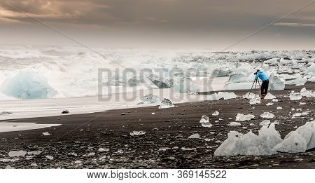 Unrecognised Photographer Capturing The Ice Chunks From The Vatnajokull Glacier During Sunset In Ice