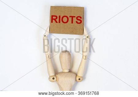 Wooden Figure Person Protester Holds Craft Brown Signboard With Word Riots In Red Color On White Bac