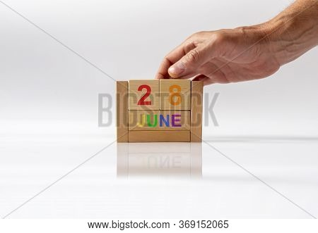 June 28 Date On Wooden Calendar In Colors Of Lgbtq Flag Colors With Male Hand On White Glossy Backgr