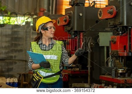 Female Worker Wearing Hard Hat Are Working In Industrial Plants That Have Machines.