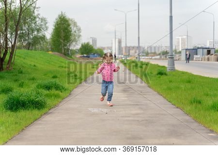 Little Girl Runs Down The Street In Summer And Laughs