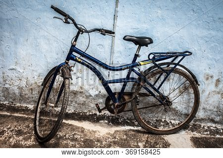 Blue And Black Colored Bicycle Against A Wall. Horizontal Shot.