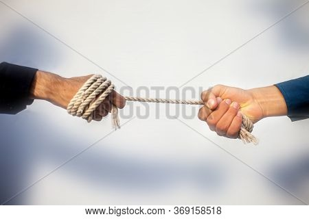 Close Up Shot Of Two Male Hand Playing Tug Of War Over Blurred Background.