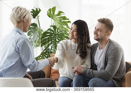 Successful Marital Therapy. Couple Shaking Hands With Family Counselor Thankful For Help And Saved M