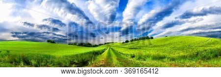 Panoramic Rural Landscape With Idyllic Vast Green Fields On Hills And Fascinating Cloudscape