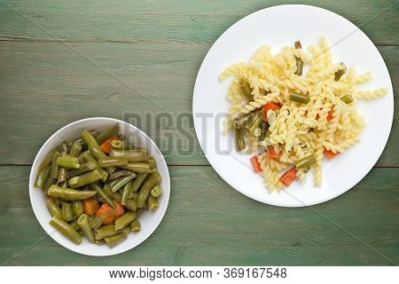 Pasta With Green Beans With Garlicand Carrots On A White Plate On A Green Wooden Background. Mediter