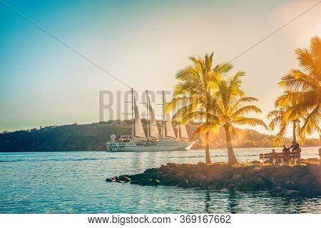 Cruise ship Luxury travel landscape boat sailing away in French Polynesia Tahiti Bora Bora island sunset. Honeymoon famous destination idyllic tropical islands.