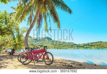 Cycling tourism e-bike bikes biking tour excursion tourists summer vacation travel landscape. Tahiti island bicycles on beach.