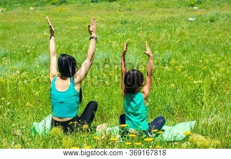Young Mother And Daughter Doing Yoga Exercises, Young Woman Doing Yoga Exercises In The Park, Mother