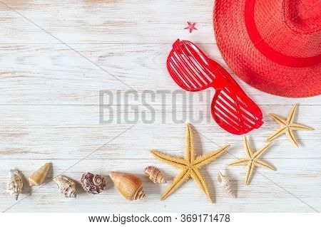 Red Color Hat, Glasses, Sea Starfishes And Seashells On Vintage Wood Board. Flat Lay Of Summer Acces