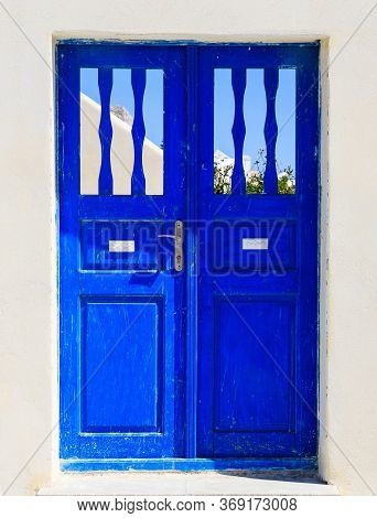 Blue Wooden Retro Door On A Whitewashed Wall. Cyclades, Greece.