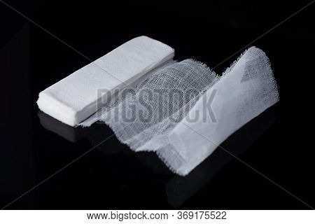 White Medical Cotton Gauze Bandage On White, Black Background, Medical Bandage Of New First Aid Gauz