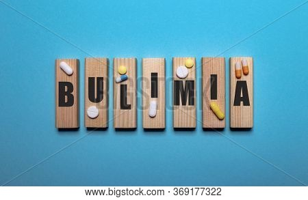 On A Blue Background On Wooden Blocks Next To Pills Is The Word Bulimia Written. Medical Concept