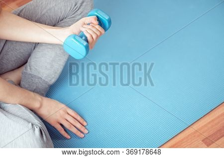 Top View Of Female Hands Holding Dumbbell. Woman Sitting On Sports Mat And Doing Strength Exercises.