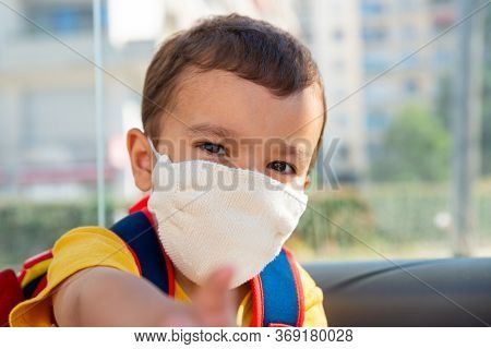 Little boy wearing white knitted cotton face mask as a protection against the novel coronavirus and Covid-19 disease.