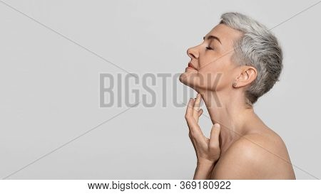 Anti-age Treatment. Profile Of Beautiful Middle-aged Woman Touching Soft Skin On Her Neck Over Light