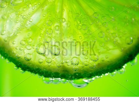 Lime slice with drop of lemon juice close-up. Fresh and juicy Citrus over green background. Dripping lime juice closeup from sliced lemon. Lemonade. Mojito. Vitamin C