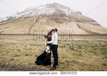 Wedding Couple On A Background Of Snowy Mountains. The Bride In A Black Dress And Groom Are Hugging