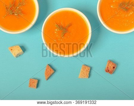Pumpkin And Carrot Soup With Fresh Dill On Blue Background