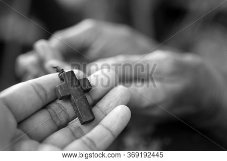 Cross In Hand. Hands Holding Jesus Christ Holy Cross Crucifix In Black And White. Believe In God And