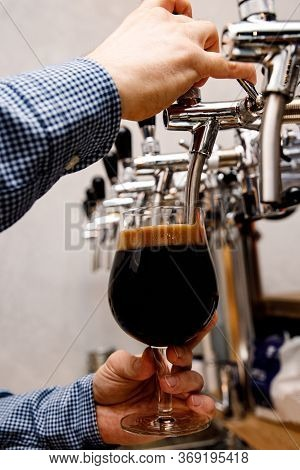 The Bartender Pours Fresh Dark Beer From Tap In The Pub.