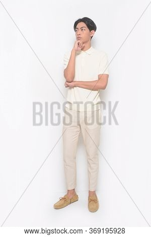 full length Portrait of handsome man wearing polo -shirt with casual trousers  brown casual shoes, put hands prop up on chins.