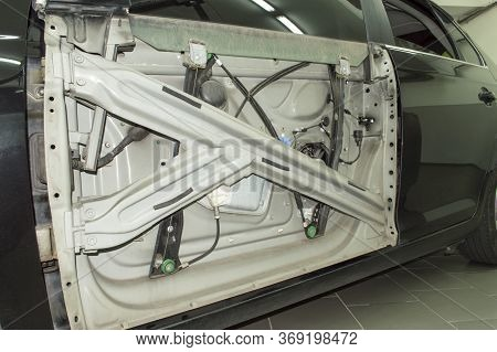The Mechanism Of The Electric Window Lifter Installed On The Front Left Door Of A Dark Gray Car With