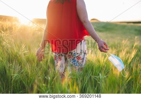 Close Up Of Unrecognizable Woman Walking Outdoors Throwing Away Her Mask. Young Happy Girl Removing