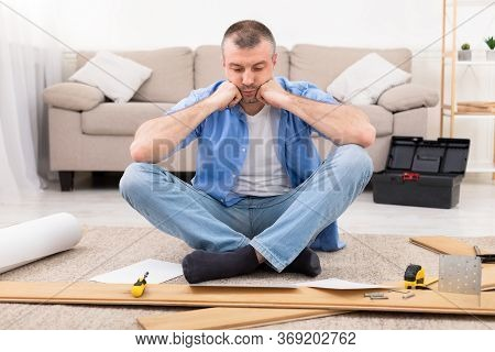 Furniture Assembly Trouble. Sad Man Sitting Near Disassembled Shelf Having Problems Installing Self-