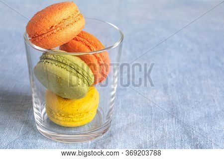 Multi-colored Macaroons In A Glass Cup On A Linen Napkin. Mcarons Or Macaroons Is French Or Italian