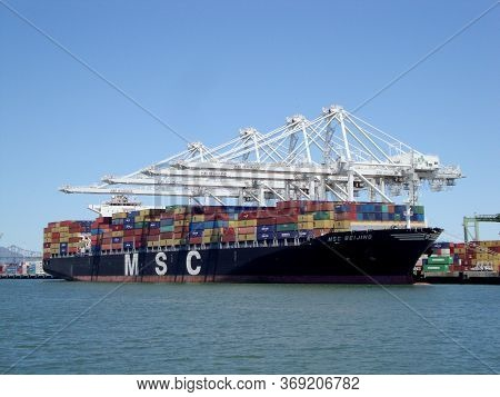 Oakland - May 23, 2010:  Msc Shipping Boat Is Unloaded By Cranes In Oakland Harbor On A Clear Day. T