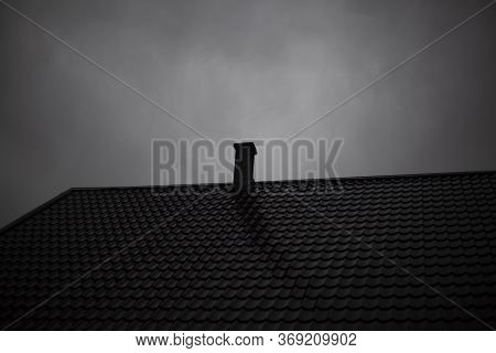 The Roof Of The House In Cloudy Weather. The Roof Of A Country House. Chimney On The Roof. Precipita