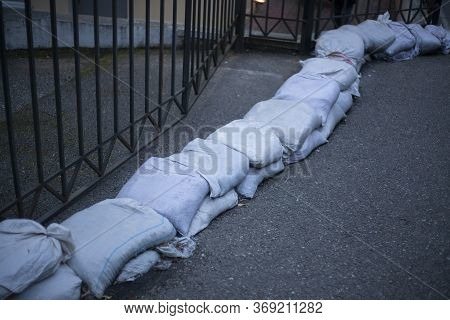 Sandbags To Protect Against Flooding By Water From The Mountains. Little Dam On The Street. Bags Lie