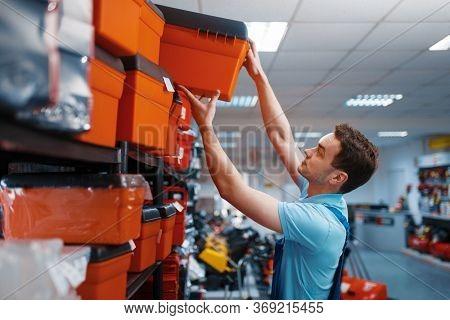Male employee choosing toolbox in tool store