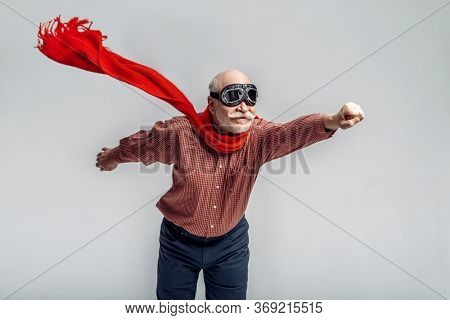 Elderly man in a red scarf and pilot glasses
