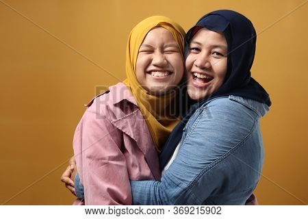 People And Family, Happy Smiling Asian Muslim Mother Hugging Daughter Against Yellow Background, Mot
