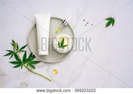 Tuba And Jar Of Cream Cbd Oil, Thc Tincture And Hemp Leaves On Marble Background. Flat Lay, Minimali