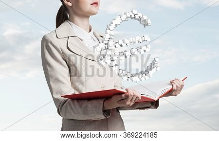 Businesswoman With Euro Currency Sign From Cubes Above Opened Notebook. Investment And Money Saving