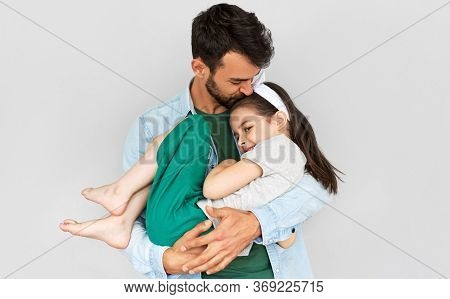 Indoor Horizontal Image Of Happy Father Embraces His Cute Daughter In His Arms. Loving Daddy And His