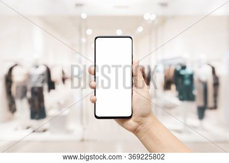 Mockup White Blank Screen Mobile Phone. Hand Holding Smartphone With Blurred Women Clothing Store Ba