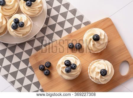 Homemade Cupcakes With Blueberry And Vanilla Cream On Porcelain Plate And Wooden Board. Flat Lay Sty