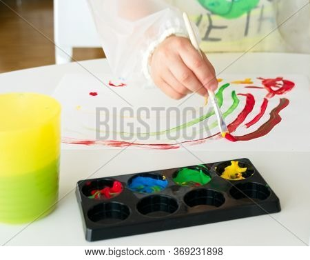 Little Boy Painting With A Brush And Tempera Paint A White Paper On A White Table With Different Con