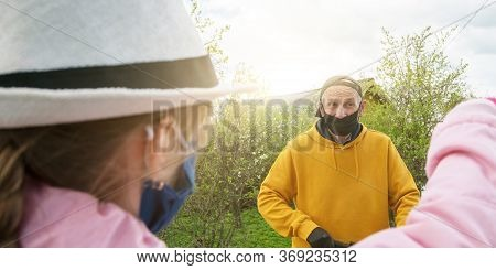 Girl In White Hat And Mask Stands Opposite Senior Man At Social Distance In Garden At Bright Back Su
