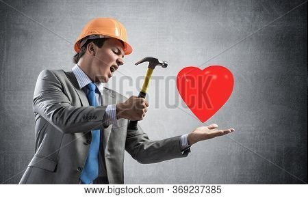 Furious Businessman Going To Crash Red Heart With Hammer. Young Handsome Man In Business Suit And Sa