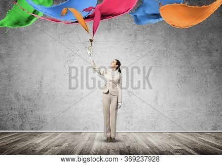 Woman Holds Trumpet Brass Instrument Over Head. Colorful Paint Splashing Out From Trumpet. Young Bus